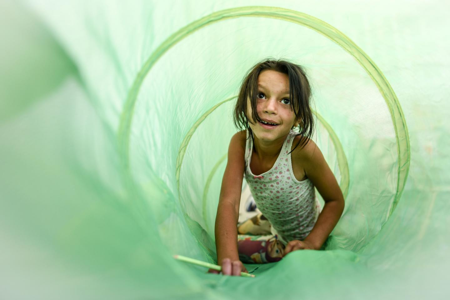 A small girl playing inside a cotton hose toy for small children called caterpillar