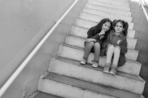Two girls sitting on stairs