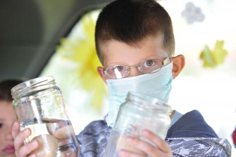 A young boy holding two jars in each hand with a mask on his face, performing scientific experiments and analyses for children