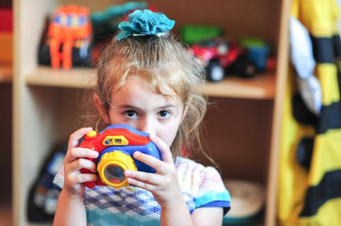 A small girl in kindergarten holding and playing with a toy photo-camera