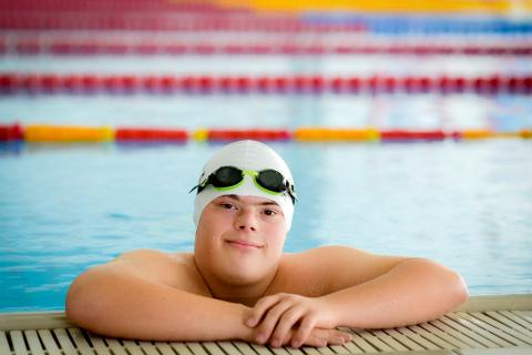 A down syndrome boy - a swimmer with a swimming hat and swimming glasses standing on the edge of a swimming pool