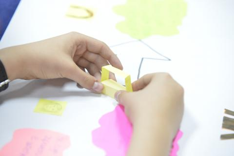 Child's hands making a mini prototype over a craft paper