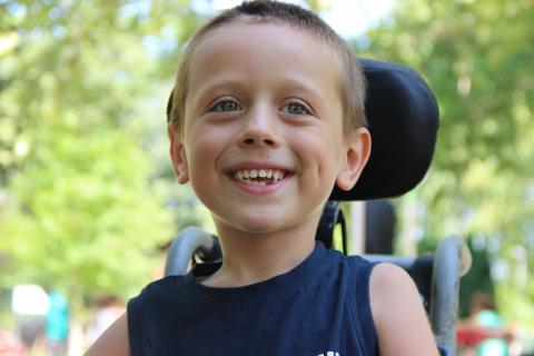 A close up photo of a boy who uses a wheelchair in a park