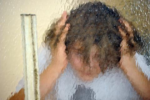 A child hiding behind a matted glass
