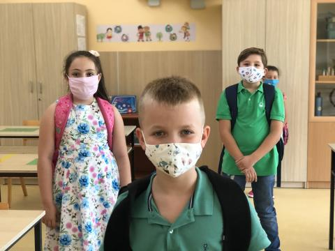 Children wearing masks stand in a classroom