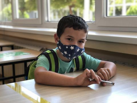 Boy with a mask sitting in a classroom holding a pen