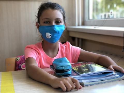 A girl with a blue mask sitting in a classroom
