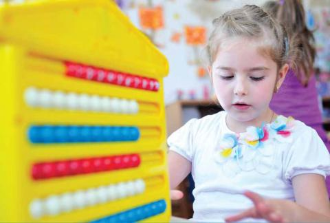 A small girl in kindergarten sitting on a table with an abacus in front of her