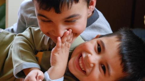 two boys hugging, playing and smiling