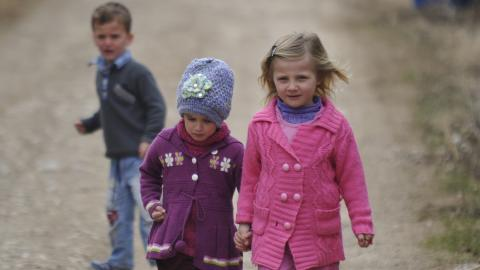 Three children walking on a dusty road, two of which are girls holding hands