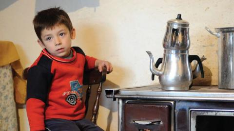 a child sitting next to a wood stove with a tea kettle on it
