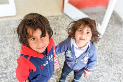 A photo of two Roma children standing in front of the clinic in Shuto Orizari