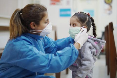 A nurse with a mask putting a mask on the face of a little girl