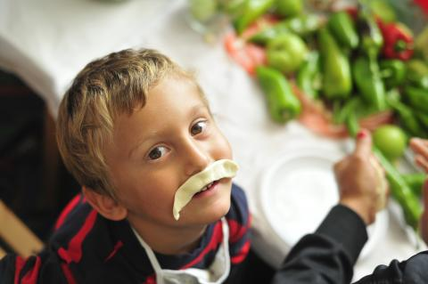 Photo of a child with a moustache made from dough during kindergarten classes focused on nutrition and food preparation