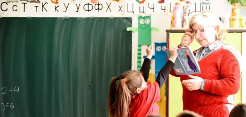 a student showing her work to a teacher in a classroom