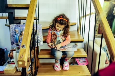 A small girl reading a booklet while sitting on stairs