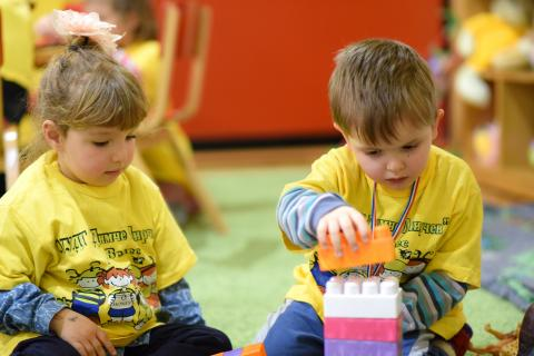 Two children in kindergarten playing with construction toys