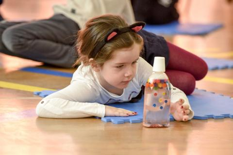 A girl looking at a diy sensory bottle