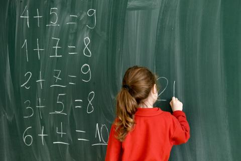 Girl in a red blouse writing on a green chalkboard
