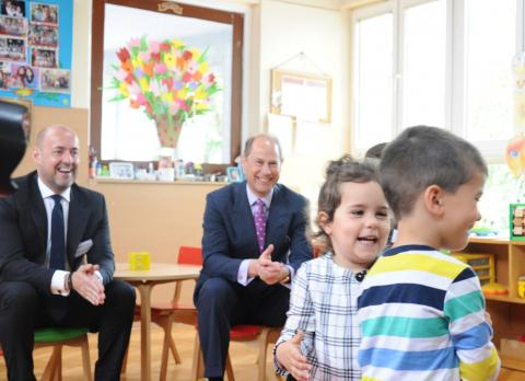 A photo of children in a kindergarten on which in behind sitting are Prince Edward and UNICEF Representative Benjamin Perks