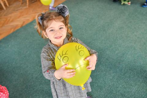 Girl holding a yellow balloon