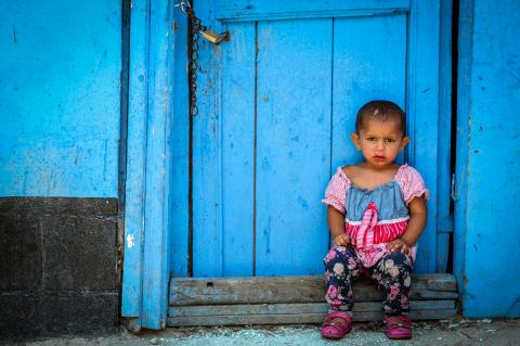 A child sitting on the doorstep of an old blue door