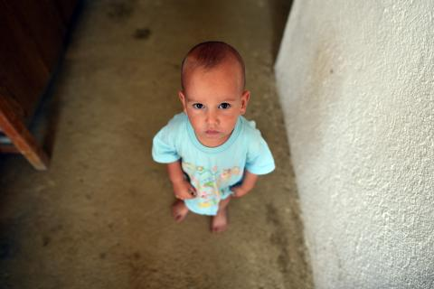 A small child standing barefoot on a concrete floor