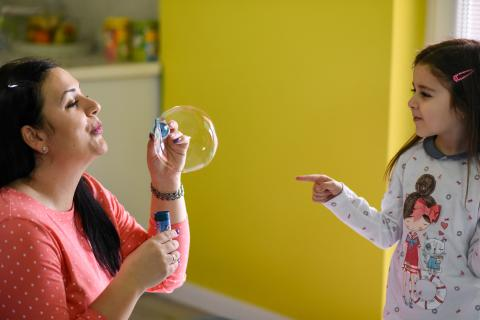 a mother and a child - small girl playing with soap bubbles