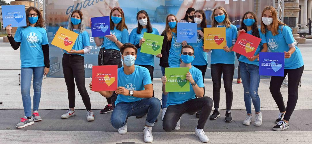 UNICEF volunteers wearing blue shirts and masks pose holding Thank you teacher signs