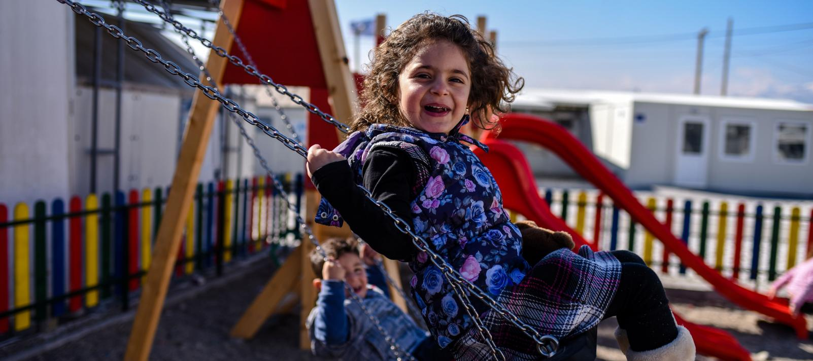 A small girl having a laughing-out-loud moment while swinging on a swing at the kids corner created by UNICEF within the refugee and transit centre Vinojug near Gevgelija
