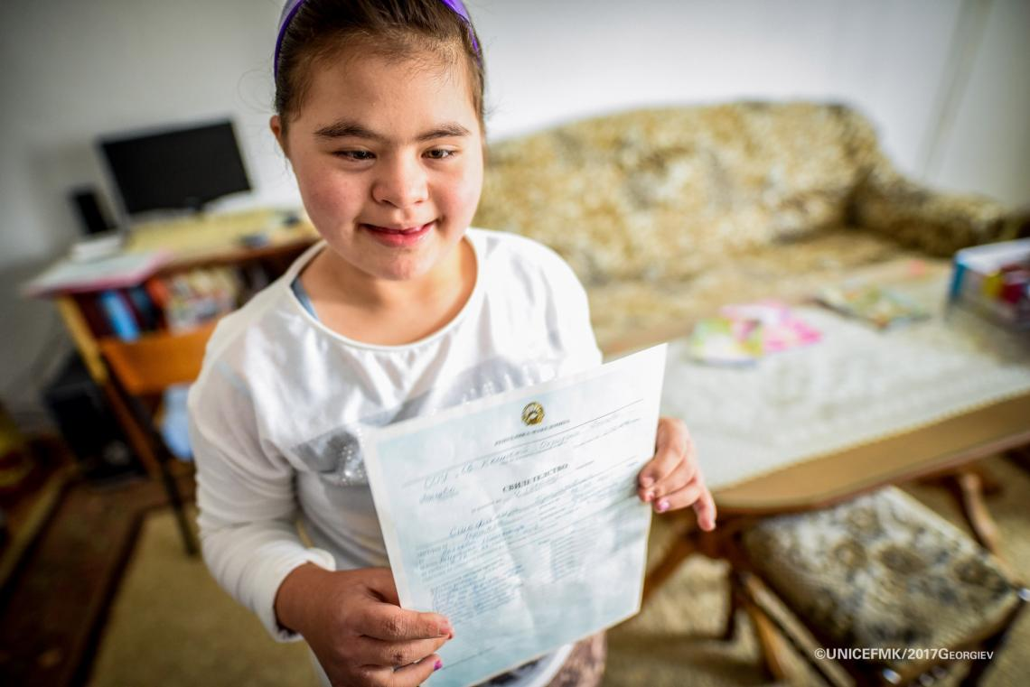 Stefanija 12 year old girl with down syndrome proudly presents her straight A's report card from school