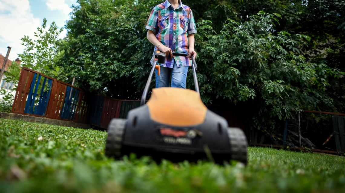 One of the boys living in the small group home in Berovo is operating a lawnmower to tidy up the grass in the backyard of the small group home.