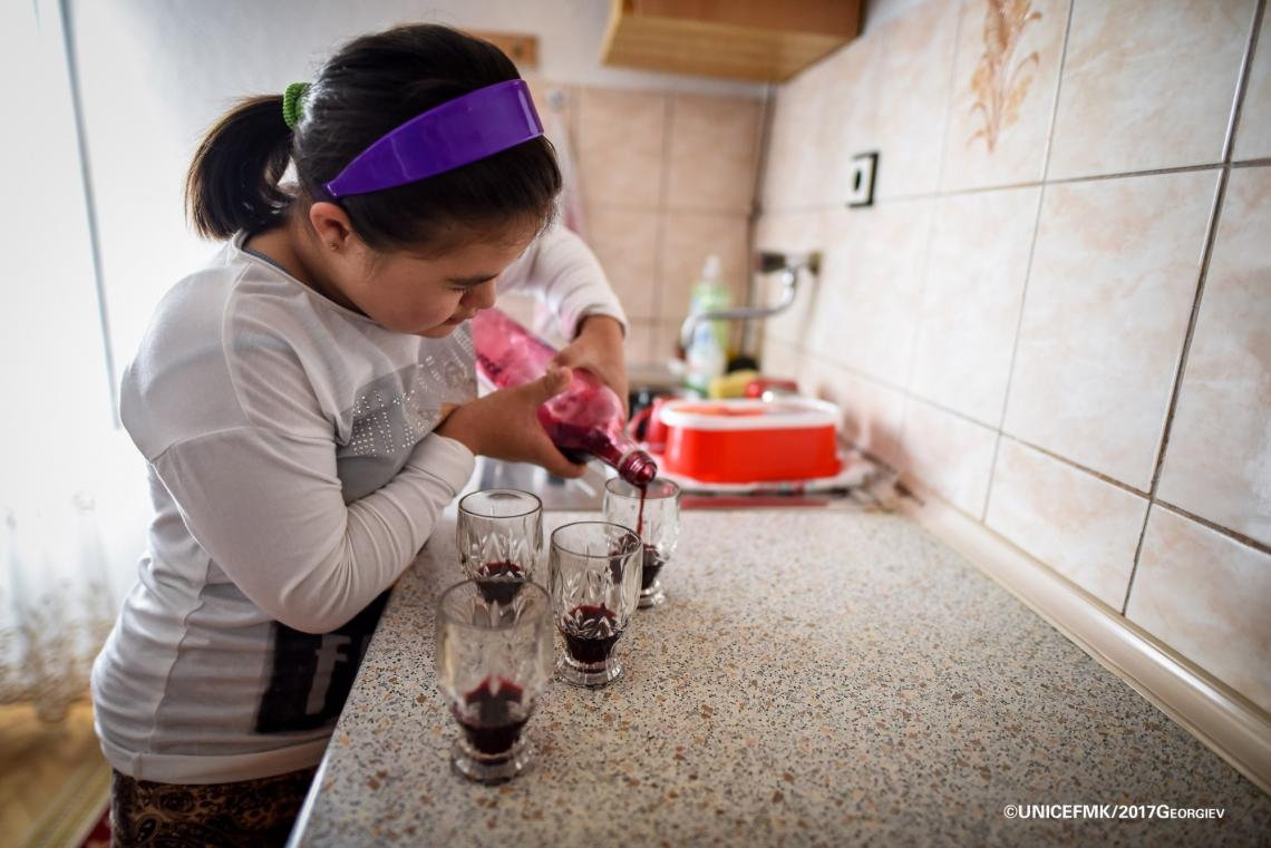 Stefanija 12 year old girl with down syndrome helps out in the kitchen by pouring some homemade juice