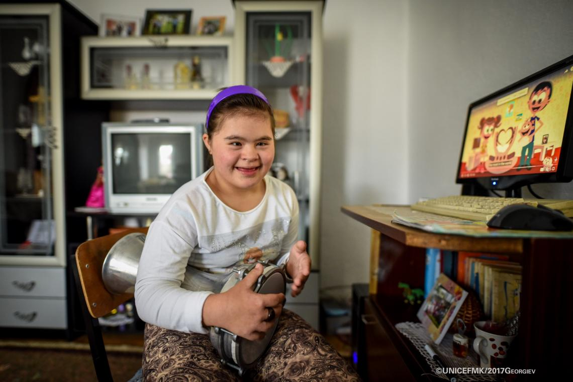 Stefanija 12 year old girl with down syndrome plays darabouka in the living room of her family house in Delcevo