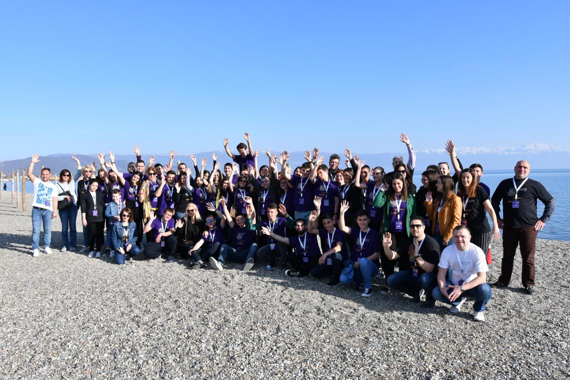 A group photo of the participants on the UPSHIFT event standing on a beach near Ohrid lake