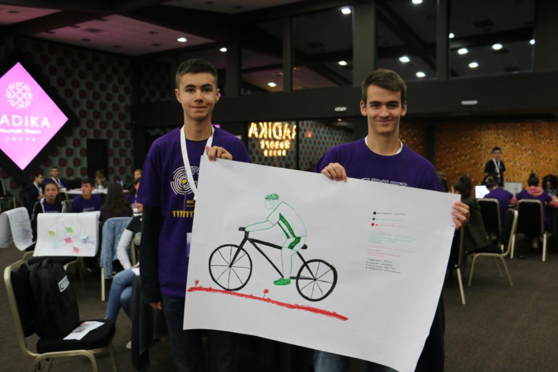 Ivan and Stefan holding a big paper sheet containing a drawing of their project idea