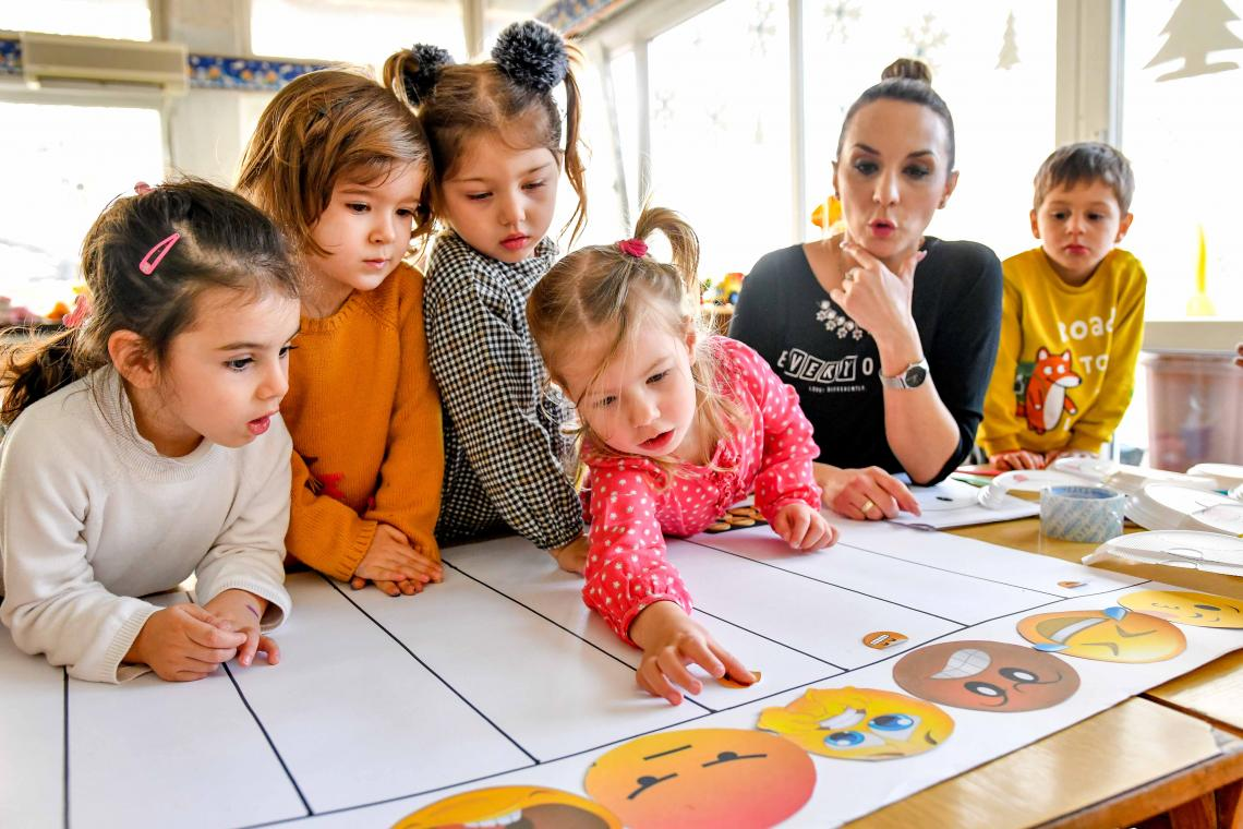 A group of children in a kindergarten looking at illustrations of different emotions with their teacher