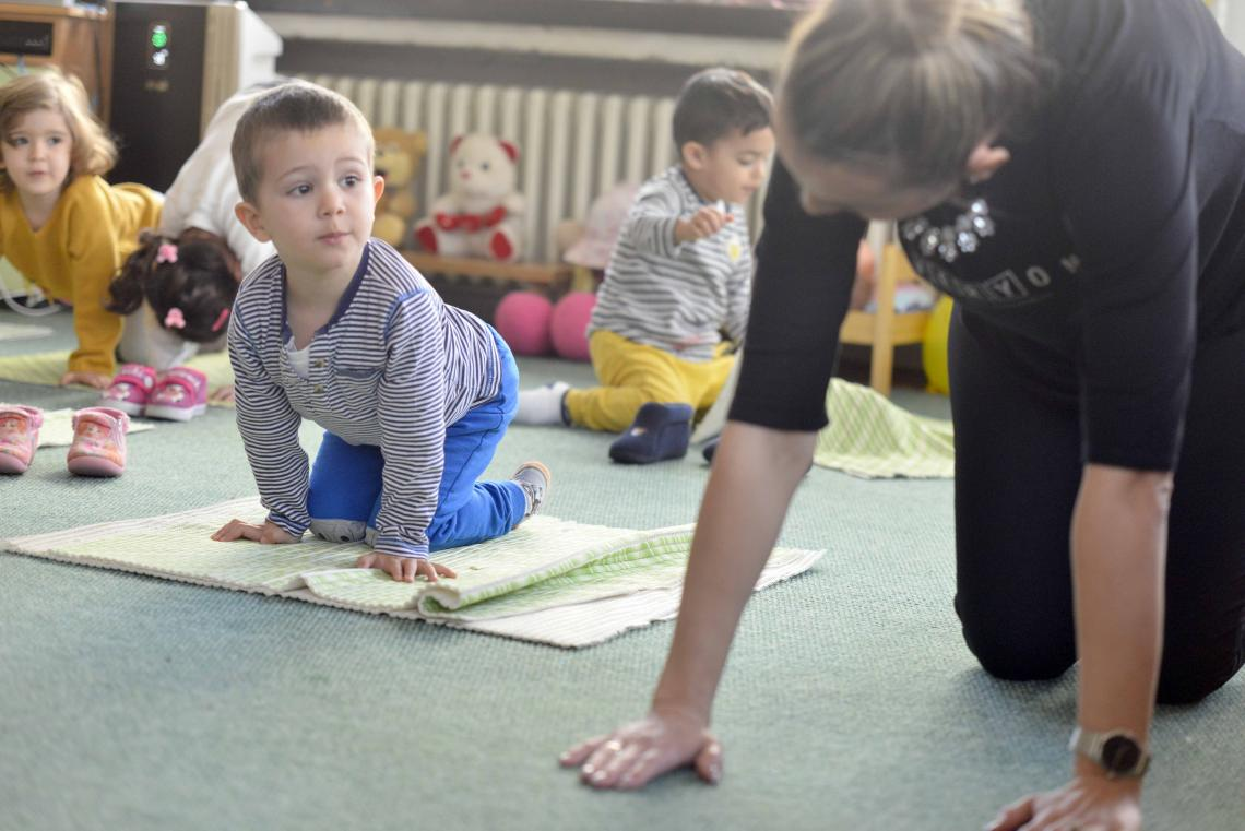 Physical exercise class in a kindergarten with children and teacher stretching