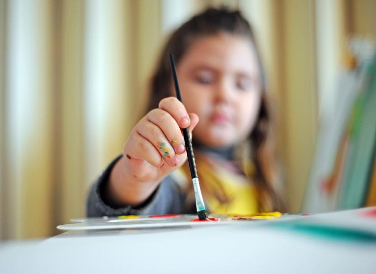 A photo of a small girl in kindergarten painting with watercolor