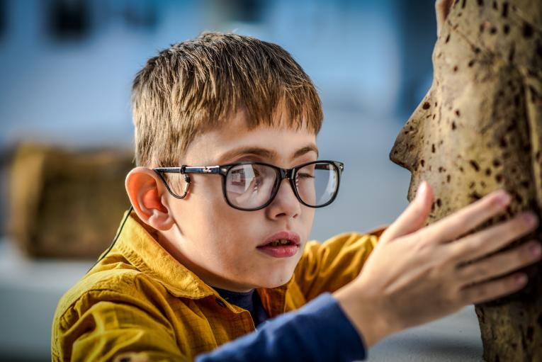 A child with visual impairment is using his hands and fingers to explore a statue