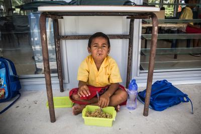 Tialeniu School student, eating noodles during class break, at Fakaofo Atoll, Tokelau.