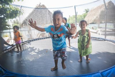 Children playing in a trampoline at a school yard of Matavala School in Atafu Atoll, Tokelau.