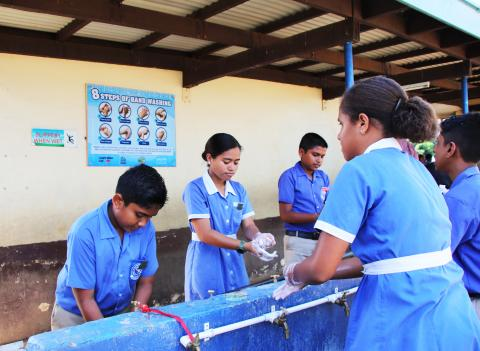 Children of Lautoka Andhra Sangam School wash their hands.