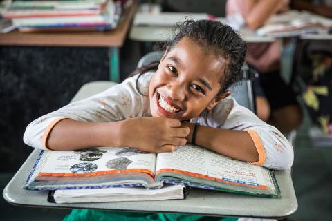 A child smiling in school.