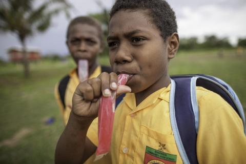 Oswin, 11, and Robert, 10, eat sugary ice sticks outside of their school in Guadalcanal, Solomon Islands.