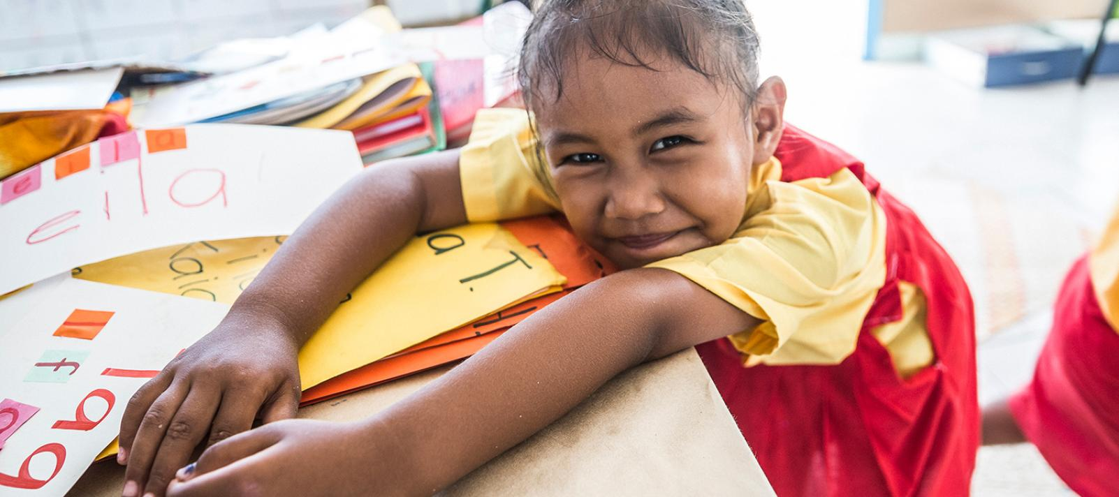 3-year-old Penina, a kindergarten Tialeniu School student posing for a photograph during class. Fakaofo Atoll, Tokelau.