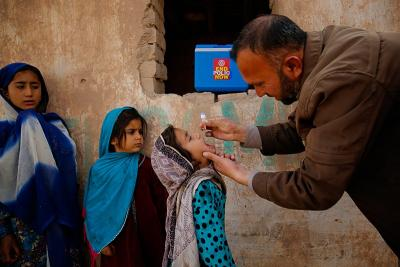 A polio vaccinator administers polio drops to a child