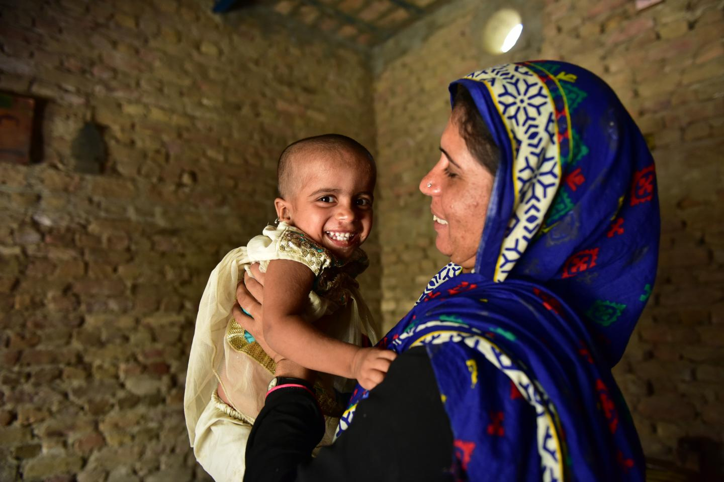 The image shows Gul Jan sharing a happy moment with her 2 year old daughter Ansa