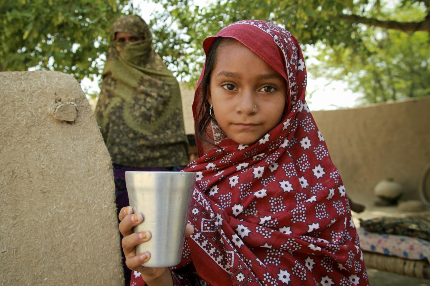 A girl holds a glass of water