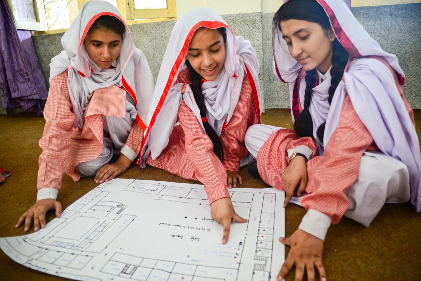 Hamna and other girls students looking at the floor plan of their school building